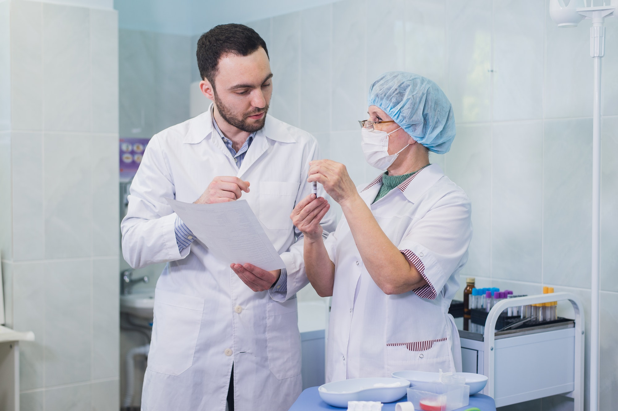 Young and senior chemists working together and looking at a test tube in a clinical laboratory